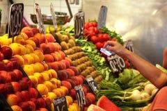 Arm der Frau Kauf auf Nahrungsmittelmarkt zahlend Stockbilder