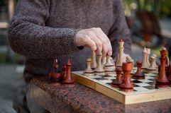 Arm des alten Mannes Schach im Park spielend Stockfoto