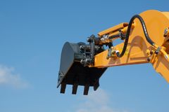 Arm of earth excavating equipment with blue sky. In background royalty free stock photos