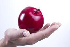 Arm en hand die een appel houden Stock Afbeeldingen