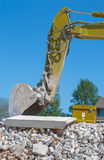 Arm of an excavator on a demolished building Royalty Free Stock Photography