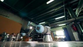 Arm för automatiserad fabrik som arbetar på en metalltabell lager videofilmer