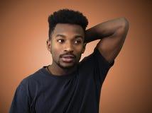 Arm för ung man bak head orange studiobakgrund arkivbilder