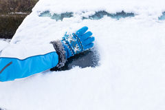 Arm with glove removing snow from car window Stock Images