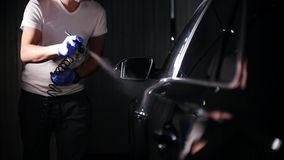 Arm hand holding industrial size spray gun for coating the car surface. Mid shot stock footage