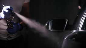Arm hand holding industrial spray gun for coating the car surface. Mid shot stock footage