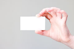 Arm holding businesscard with empty place. Bussines card in hand for your information and logo in a grey background Royalty Free Stock Image
