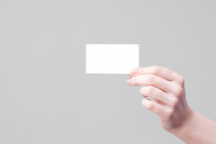 Arm holding businesscard with empty place. Bussines card in hand for your information and logo in a grey background Royalty Free Stock Photography
