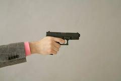 Arm holding gun. Businessman arm holding gun aiming somewhere Royalty Free Stock Photo