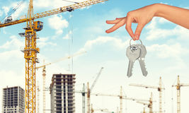 Arm holding keys on construction site background Stock Photo