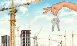 Arm holding keys on construction site background Stock Photo
