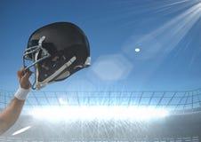 Arm holding up american football helmet. Digital composite of arm holding up american football helmet Stock Photos
