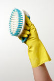 Arm holding up a scrub brush. Over white Stock Photography
