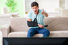 The arm injured man sitting on the sofa watching tv. Arm injured man sitting on the sofa watching tv royalty free stock images
