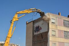 Arm of machine demolishing an apartment building royalty free stock images