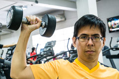 Arm of man lifting weights and exercising Stock Photos