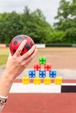Arm med bollen som ska kastas av kulöra kvarter Arkivfoton