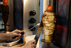 An arm moving to cut the kebab meat Stock Photography