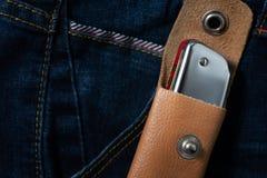 Arm?nica en la envoltura de cuero en la mezclilla azul foto de archivo libre de regalías
