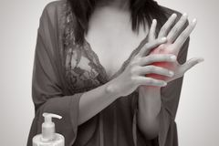 Arm pain. Asian woman in nightwear holding her hand against gray background ,De Quervain`s tenosynovitis, Pain concept stock image
