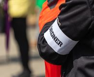 Arm of a person with a black jacket, on which a white bandage with the German inscription. `Guard` and above it the name of the city of Wolfsburg are applied stock photography