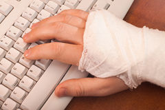 Arm in plaster on the keyboard Stock Photos