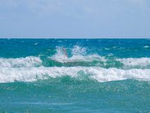 The arm protrudes from the water in the sea waves and splashes. royalty free stock photography