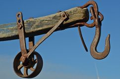 Arm, Pulley, and Wheel of a Winch system. An old-fashioned pulley system for lifting docks consists of a wooden block, hook, and pulling Stock Photos