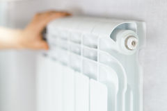 Arm put on  heating white radiator. Royalty Free Stock Photo