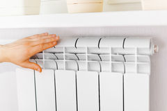 Arm put on  heating white radiator. Stock Photo