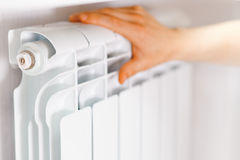 Arm put on  heating white radiator. Royalty Free Stock Images