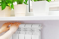 Arm put on  heating white radiator.Windowsill with flowers. Royalty Free Stock Photo