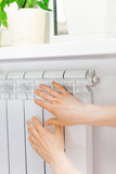 Arm put on  heating white radiator.Windowsill with flowers. Stock Photography