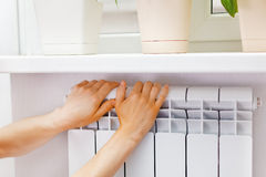 Arm put on  heating white radiator.Windowsill with flowers. Stock Image