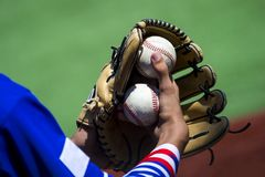 An arm stretches out to catch a baseball using a worn leather glove. royalty free stock photos