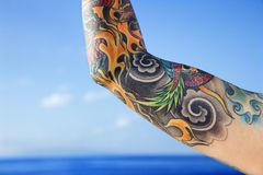 Arm of tattooed woman. Stock Photos