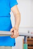 Arm und Hand der alten Frau auf horizontaler Stange Stockfoto
