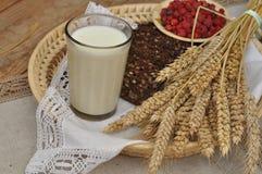 Arm voll Ohren, frisches Brot, Himbeeren und Glas Milch auf einem Strohbehälter mit einer Leinenserviette Lizenzfreie Stockbilder