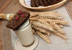 Arm voll Ohren, frisches Brot, Himbeeren und Glas Milch auf einem Strohbehälter mit einer Leinenserviette Lizenzfreies Stockfoto