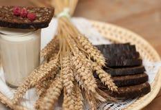 Arm voll Ohren, frisches Brot, Himbeeren und Glas Milch auf einem Strohbehälter mit einer Leinenserviette Stockfotografie