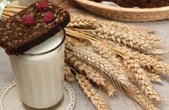 Arm voll Ohren, frisches Brot, Himbeeren und Glas Milch auf einem Strohbehälter mit einer Leinenserviette Lizenzfreie Stockfotos