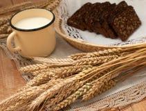 Arm voll Ohren, frisches Brot und Glas Milch auf einem Strohbehälter mit einer Leinenserviette Stockfoto