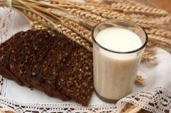 Arm voll Ohren, frisches Brot und Glas Milch auf einem Strohbehälter mit einer Leinenserviette Lizenzfreies Stockbild