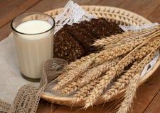Arm voll Ohren, frisches Brot und Glas Milch auf einem Strohbehälter mit einer Leinenserviette Stockfotografie
