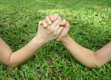 Arm wrestle on the grass. Two children arm wrestling stock photography