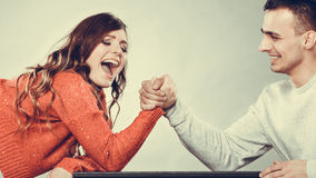 Arm wrestling challenge between young couple Stock Photos