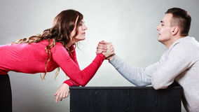 Arm wrestling challenge between young couple. Partnership relationship concept. Girlfriend confronts his boyfriend. Woman and men arm wrestling challenge between Royalty Free Stock Photos