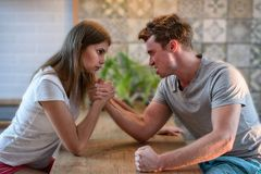 Arm wrestling challenge between young man and woman, couple household conflict and fight. Arm wrestling challenge between young men and woman, couple household royalty free stock photography