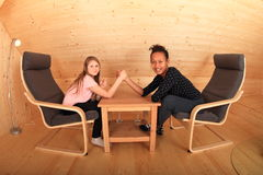Arm wrestling. Girls trying arm wrestling - smiling Caucasian kid and young Papuan women sitting in armchairs in wooden attic room Stock Image