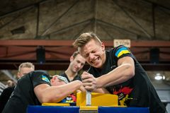 Arm wrestling match between Sweden and Ukraine. STOCKHOLM, SWEDEN - JANUARY 13, 2018: Profile view of a Swedish and Ukrainian male arm wrestler in a match at Stock Photography